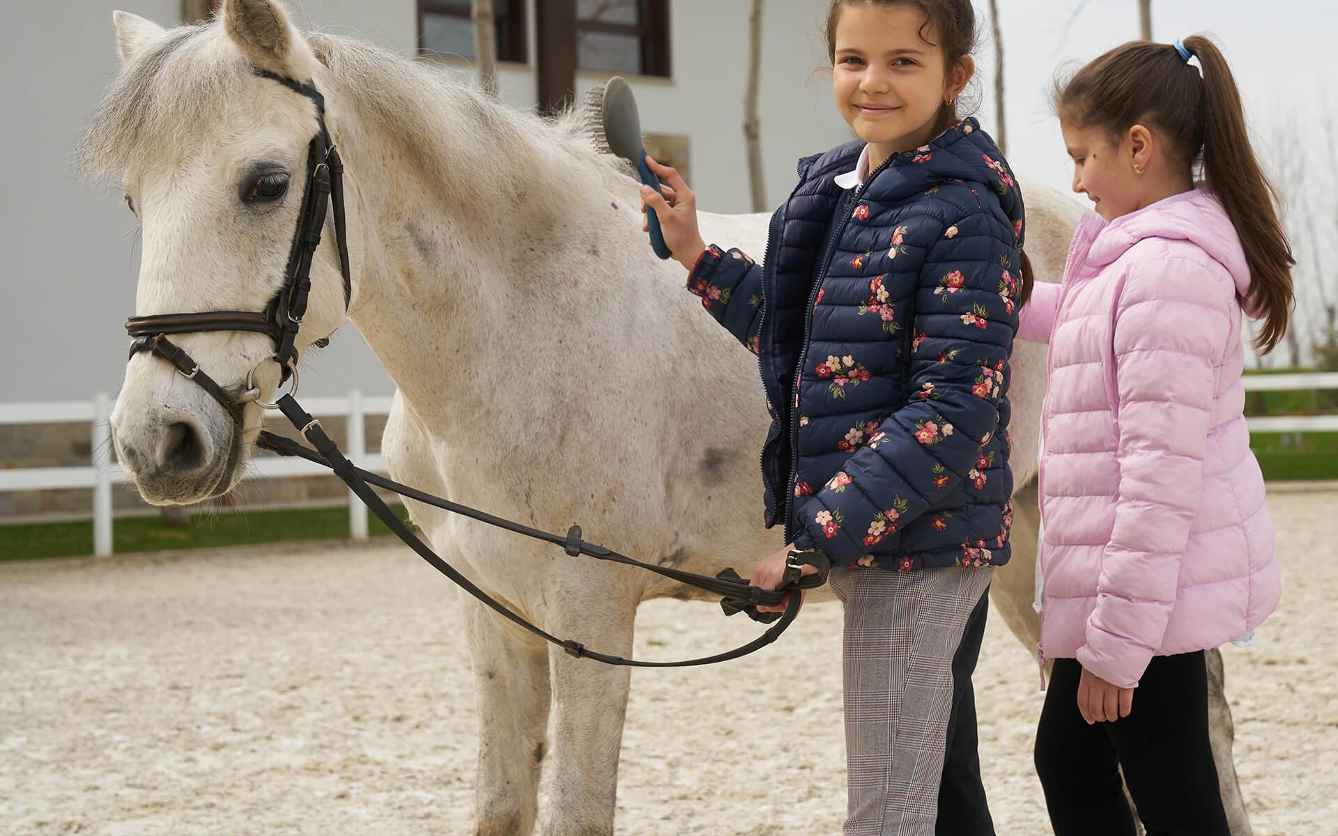 Две малки момичета решат бяло пони