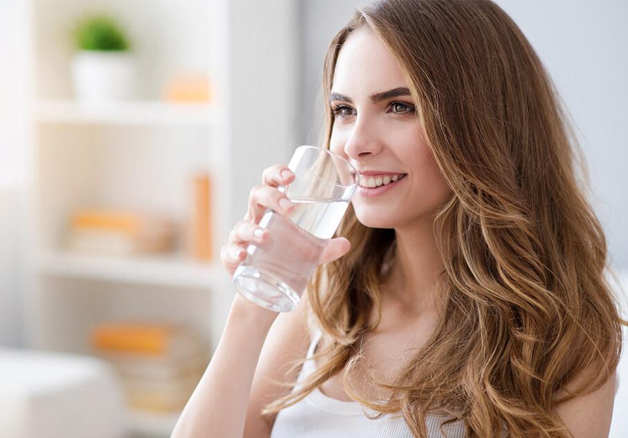 Млада жена, която пие вода