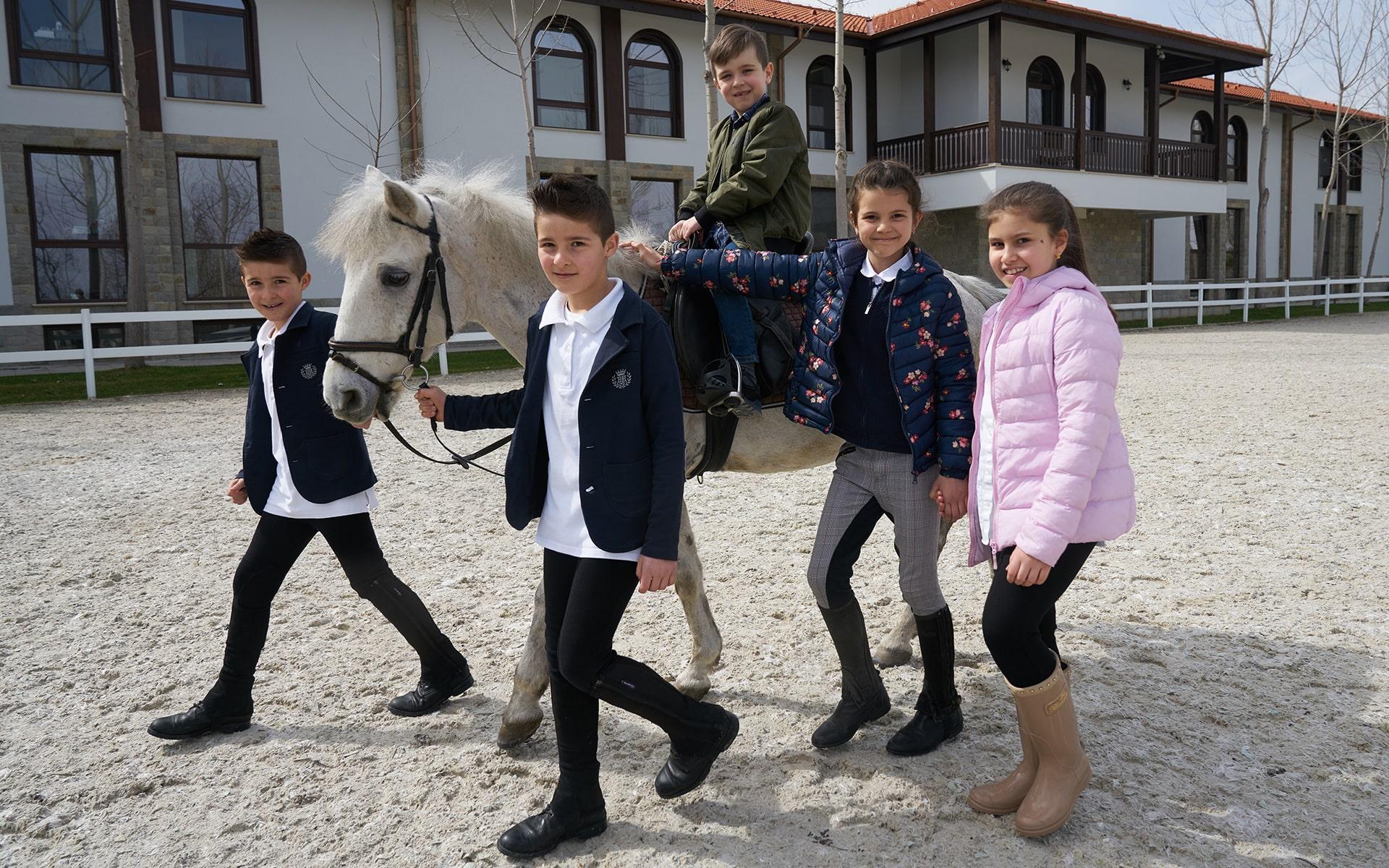 Деца, които се радват на малко пони