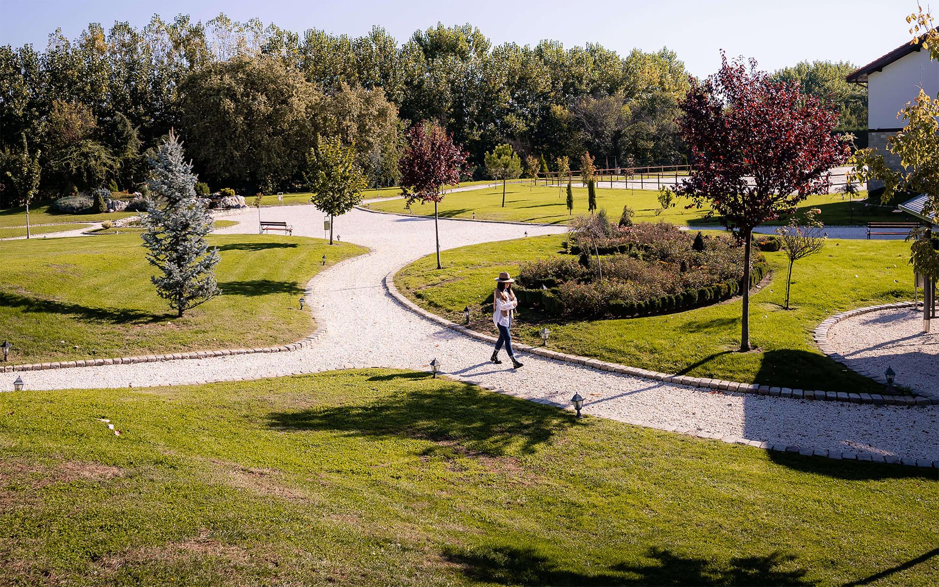 """Момиче се разхожда в градините на комплекс """"Тракиец""""."""