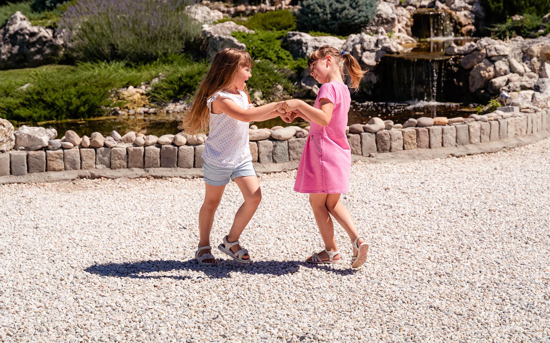 Две момиченца играят навън
