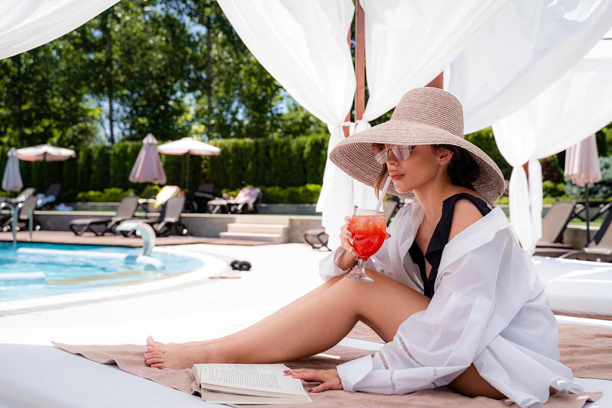 Жена пие коктейл на басейн
