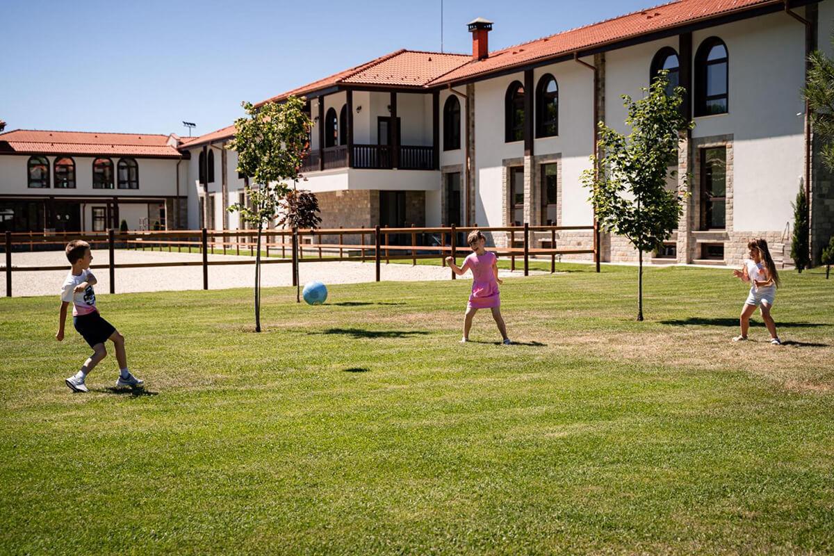 деца играят на тревата с топка
